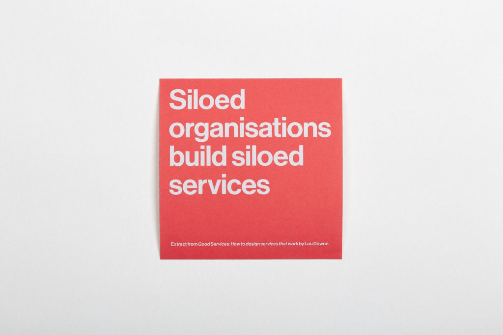 "A bright orange square sticker with the words, ""Siloed organizations build siloed services"" in white type."